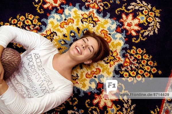 Young woman lying on patterned rug laughing