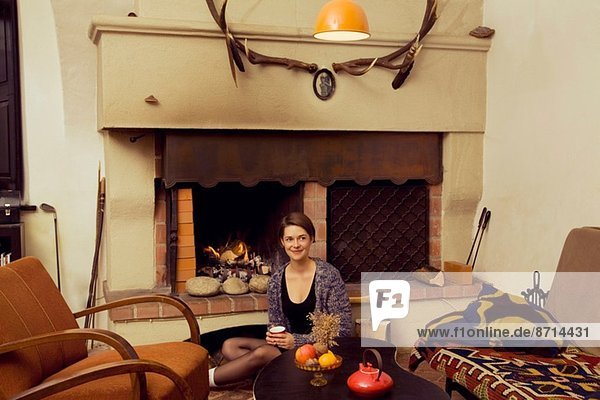 Portrait of young woman sitting on floor next to fireplace