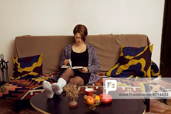 Young woman relaxing on sofa reading her book