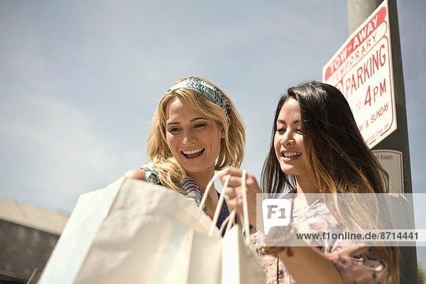 Zwei junge Frauen auf der Straße suchen in Einkaufstaschen
