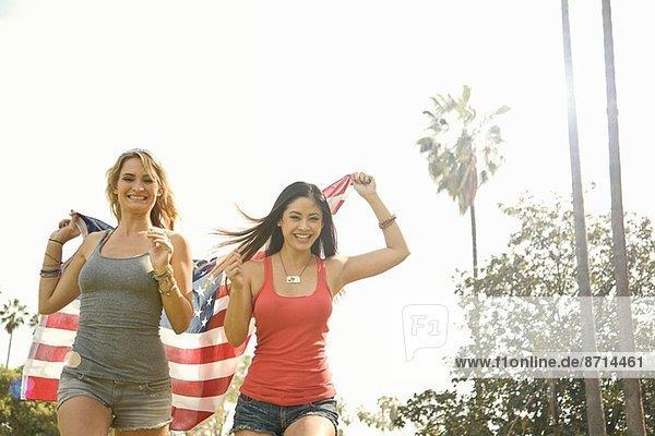 Zwei junge Frauen laufen mit amerikanischer Flagge im Park.