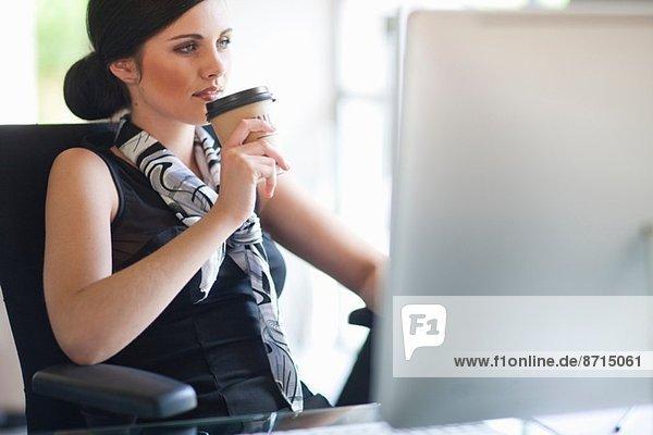 Junge Geschäftsfrau bei einer Kaffeepause am Schreibtisch