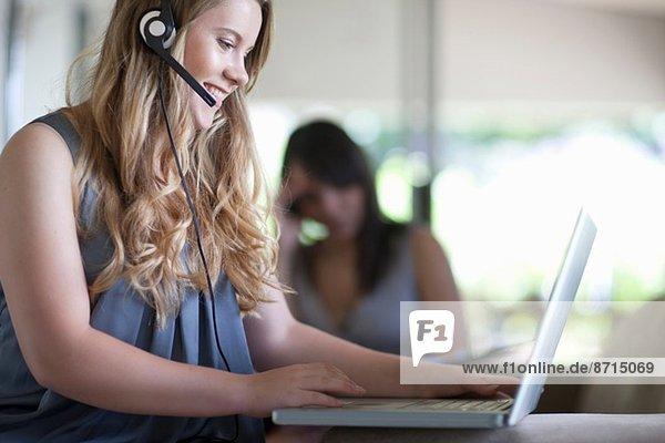 Junger Büroangestellter spricht am Headset  während er am Laptop sitzt.