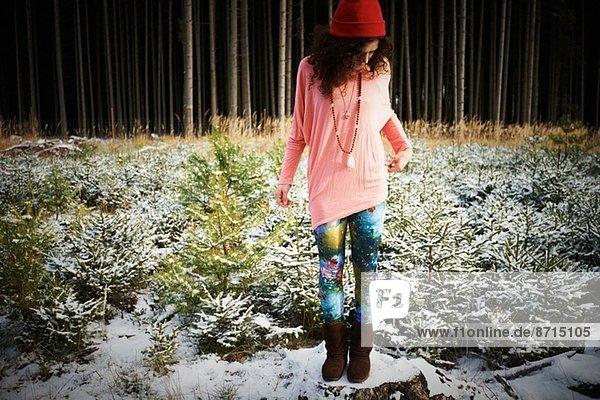 Mittlere erwachsene Frau mit Hut  stehend auf schneebedecktem Boden