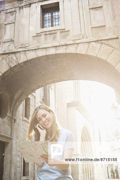 Junge Frau auf der Karte vor der Kathedrale von Valencia  Valencia  Spanien Junge Frau auf der Karte vor der Kathedrale von Valencia, Valencia, Spanien