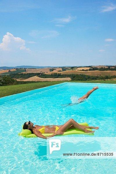 Mittlere erwachsene Frau auf einer aufblasbaren Matratze im Schwimmbad liegend