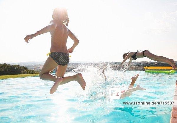 Drei Leute springen in den Swimmingpool