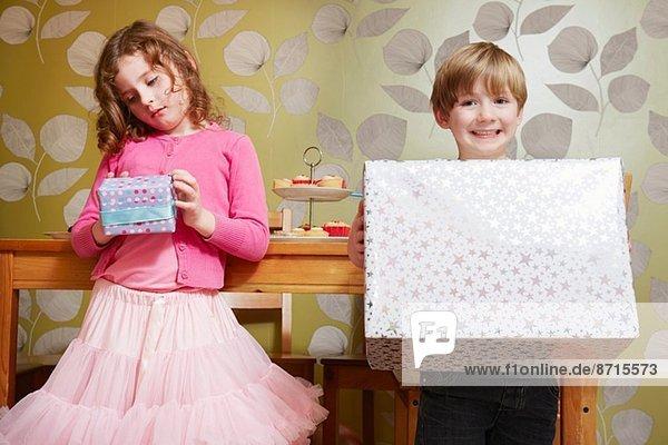 Junge und Mädchen mit großem und kleinem Geschenk Junge und Mädchen mit großem und kleinem Geschenk