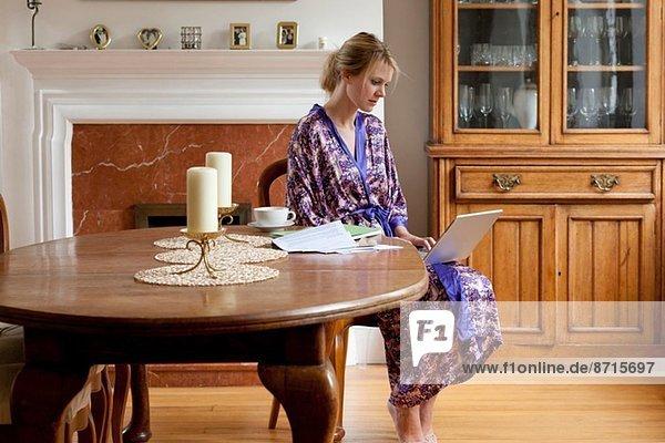 Junge Frau zu Hause im Morgenmantel bei der Arbeit am Laptop