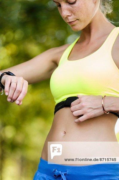 Junge Sportlerin beim Überprüfen von Herzfrequenzmessgeräten