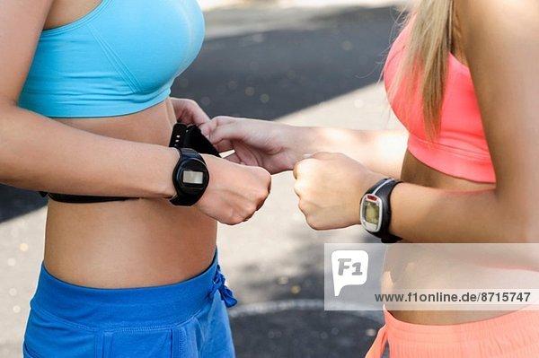 Junge Athletinnen beim Überprüfen der Herzfrequenzmessung