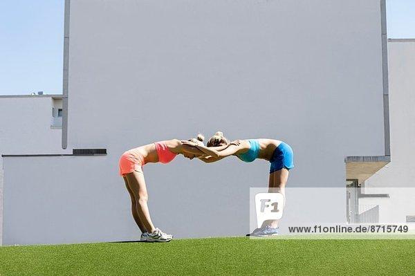 Zwei junge Sportlerinnen beim gemeinsamen Training im Park