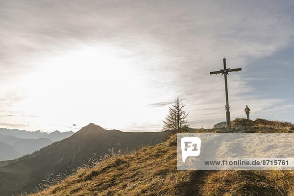 Silhouette der mittleren erwachsenen Frau und Holzkreuz  Achensee  Tirol  Österreich
