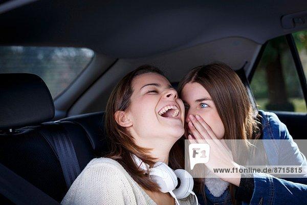 Schwestern flüstern im Auto