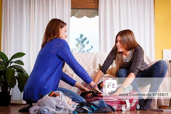 Schwestern beim Packen von Gepäck im Zimmer