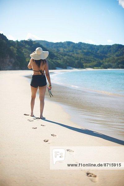 Woman on New Chums beach  Coromandel Peninsula  New Zealand