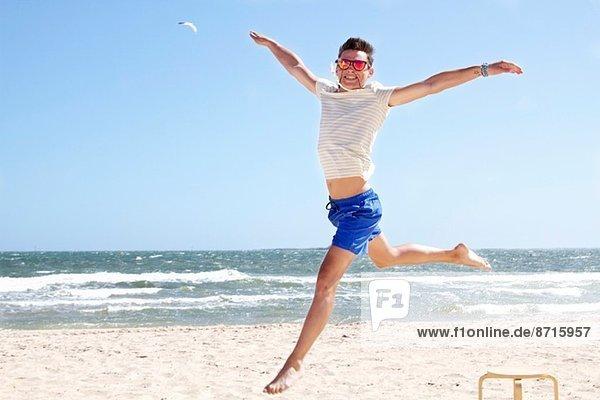Junger Mann springt am Strand  Port Melbourne  Melbourne  Australien