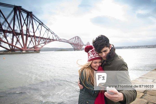 Ein junges Paar posiert vor der Forth Rail Bridge in Queensferry  nahe Edinburgh  Schottland.