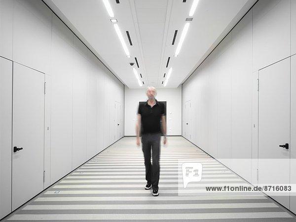 Schwarz gekleideter Mann geht durch einen weißen Korridor