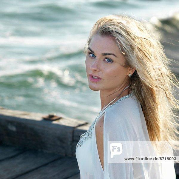 Porträt einer jungen Frau an der Küste