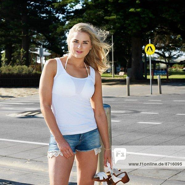 Porträt einer jungen Frau auf dem Bürgersteig