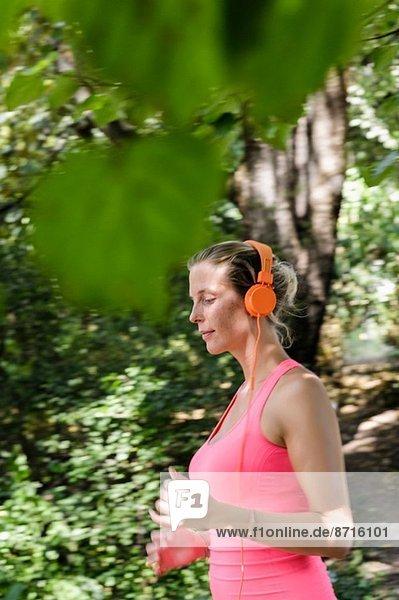 Junge Frau läuft durch den bewaldeten Park