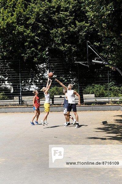 Gruppe von Freunden spielt Basketball auf dem Platz im Park