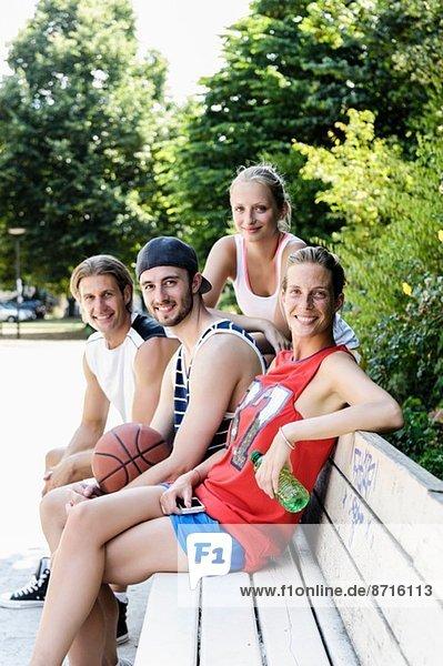 Porträt von vier Basketballspielern bei einer Pause im Park