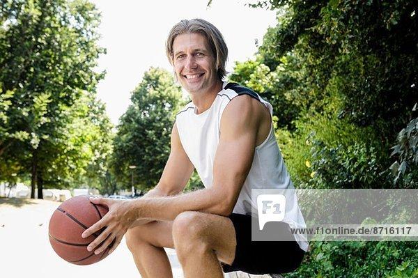 Portrait eines männlichen Basketballspielers bei einer Pause im Park