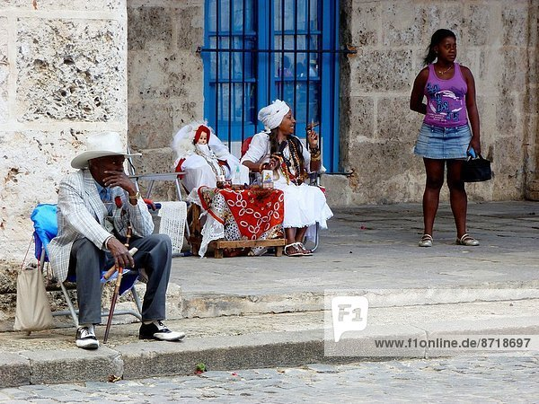 Cubans sitting in chairs on the streets of Havana  Cuba.