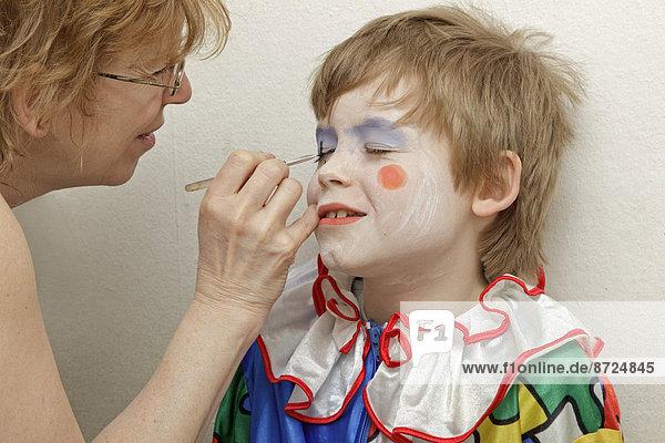 Kleiner Junge als Clown verkleidet  wird von seiner Mutter geschminkt