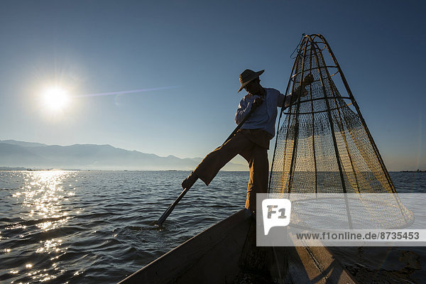 Fisherman in the morning light  leg rower with a traditional basket on the canoe  at sunrise  Inle Lake  Shan State  Myanmar