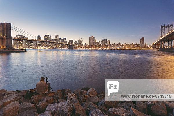 USA  New York City  Mann fotografiert Manhattan Bridge und Brooklyn Bridge