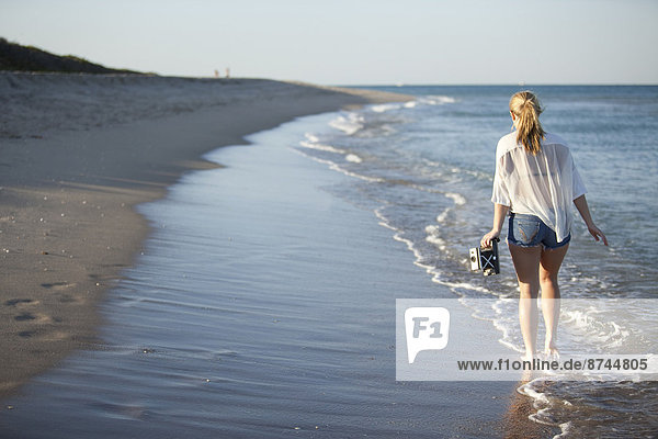 Young Woman Carrying Camera while Walking along Beach  Palm Beach Gardens  Palm Beach  Florida  USA