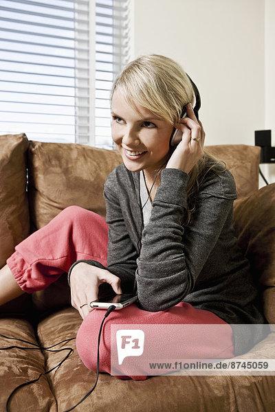 Interior  zu Hause  Frau  zuhören  Couch  Spiel  jung  MP3-Player  MP3 Spieler  MP3 Player  MP3-Spieler