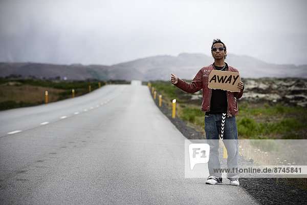 Young Man Hitchhiking with Cardboard Sign  Iceland