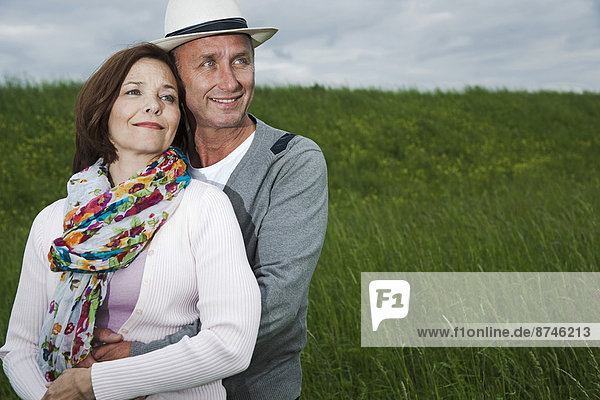 Close-up portrait of mature couple standing in field of grass  embracing  Germany