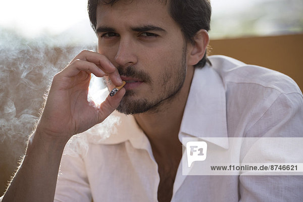 Close-up Portrait of Young Man Smoking a Cigarette  Italy