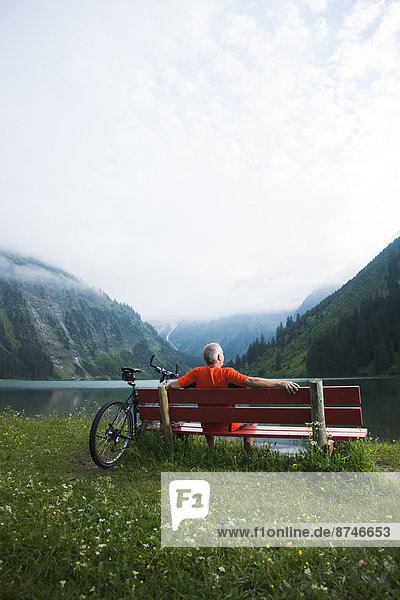 Mature Man on Bench by Lake with Mountain Bike  Vilsalpsee  Tannheim Valley  Tyrol  Austria
