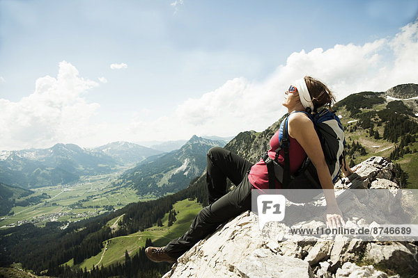 Mature woman sitting on cliff  hiking in mountains  Tannheim Valley  Austria