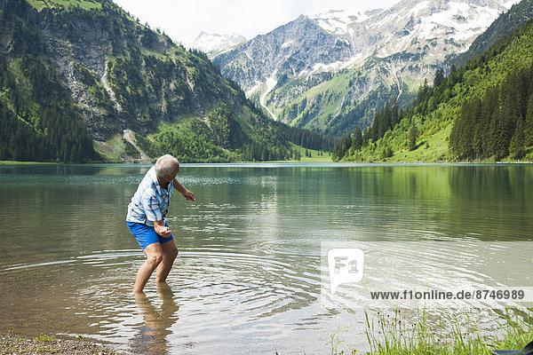 Mature man skipping stones at Lake Vilsalpsee  Tannheim Valley  Austria
