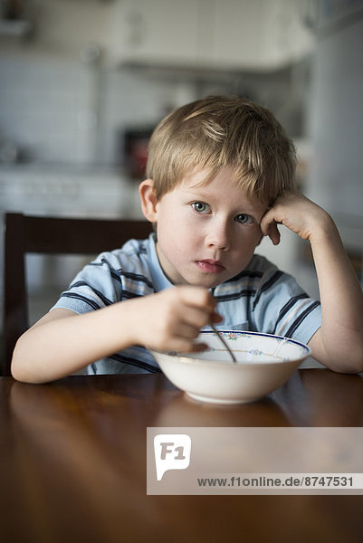 Junge - Person  Küche  Dänemark  Kopenhagen  Hauptstadt  jung  essen  essend  isst  Tisch  Frühstück
