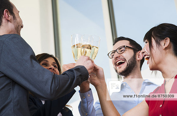 Business people holding champagne glasses and toasting each other in office  Germany