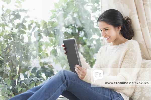 benutzen  Frau  Sitzmöbel  Fenster  Hispanier  Tablet PC  Sitzplatz
