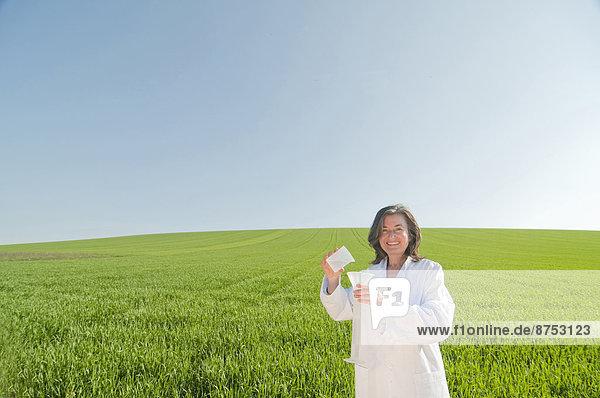 weibliche Wissenschaftler mit Reagenzglas in grünen Wiese weibliche Wissenschaftler mit Reagenzglas in grünen Wiese