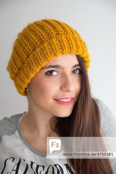 Young woman wearing knitted hat  smiling and looking at the camera.