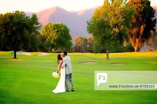 happy couple embracing after wedding ceremony  on a lush golf course / mountains setting