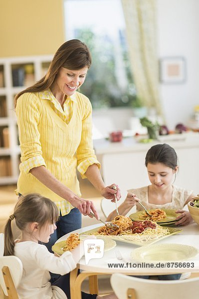 Mother and daughters (4-5 8-9) eating pasta