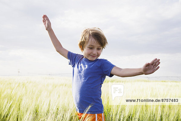 Boy (4-5) standing in grass with raised arms