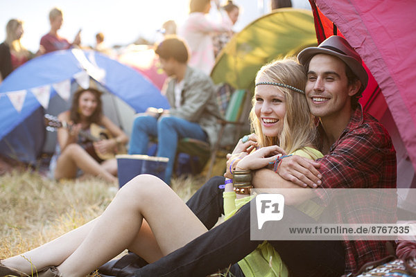 Couple hugging outside tent at music festival